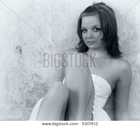 Beautiful Girl Sitting At A Wall