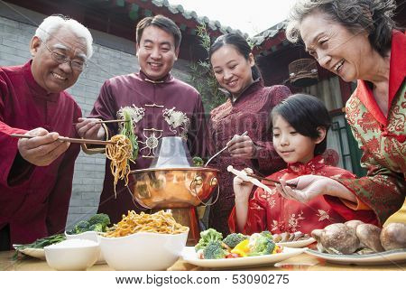 Family enjoying Chinese meal in traditional Chinese clothing