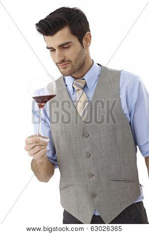 Male wine-taster holding glass of red wine, ventilating.