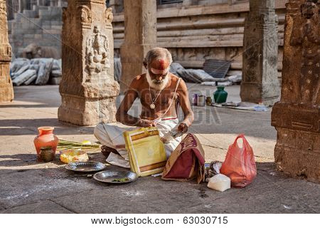 MADURAI, INDIA - FEBRUARY 16, 2013: Indian brahmin (traditional Hindu society) priest with donation in famous Meenakshi Amman Temple - historic Hindu temple located in temple city Madurai