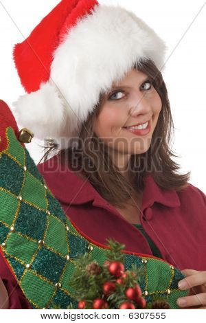 Young woman holds a Christmas stocking near a Christmas tree