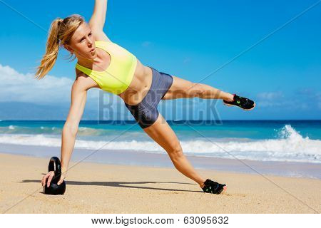 Young attractive woman doing kettle bell exercises outside. Fitness woman working out at the beach. exercise.