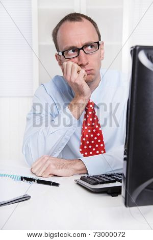 Young businessman with glasses and bald sitting in his office in a blue shirt with red tie - thinking about his future.