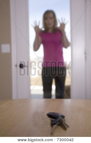 Woman Looking Through Door At Keys