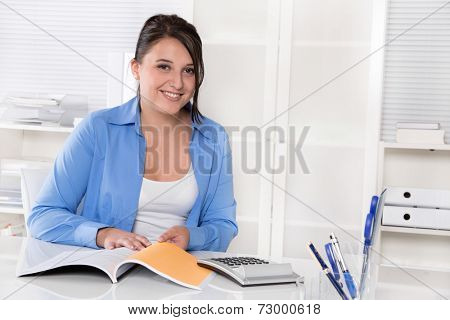 Smiling young woman at desk - stock photo with release.