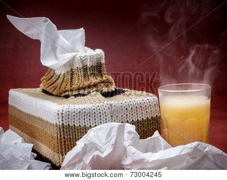 Tissue box in knit encasement and hot flu medicine drink over dark red background