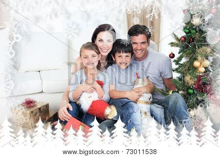 Happy family at Christmas time holding lots of presents against fir tree forest and snowflakes