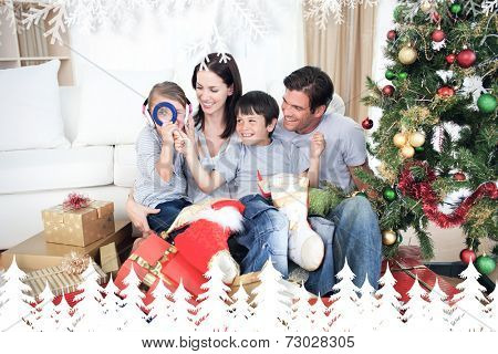 Happy family having fun with Christmas presents against fir tree forest and snowflakes