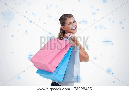 Back view of a cheerful woman holding shopping bags against snow falling
