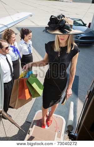 Full length of rich woman carrying shopping bags while boarding private jet with pilot and airhostess standing by at airport terminal