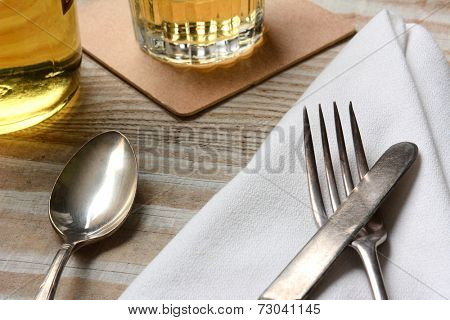 Closeup of a table setting. Old silverware, napkin and drinks on a white wood table. Horizontal format.