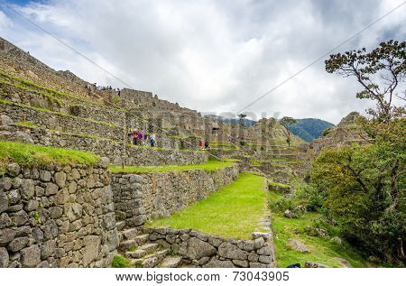 MACHU PICCHU, PERU - MAY 3, 2014 - crowds of tourist explore ruins of old city early in the morning