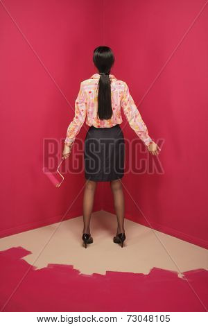 Rear view of woman painting herself into a corner
