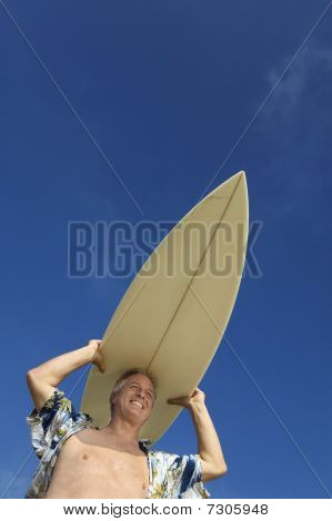Male surfer carrying surfboard on head (low angle view)