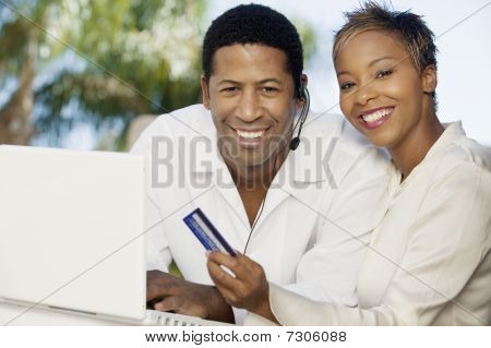 Couple on patio making online credit card purchase portrait