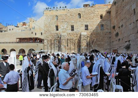 JERUSALEM, ISRAEL - SEPTEMBER 20, 2013:The Western Wall of the Temple in Jerusalem. Morning Sukkot. Many religious Jews in traditional robes tallit gathered for prayer.