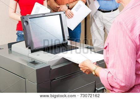 Closeup of a senior woman casting her ballot on a new electronic voting machine.