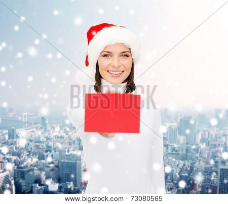 christmas, holdays, people, advertisement and sale concept - happy woman in santa helper hat with blank red card over snowy city background