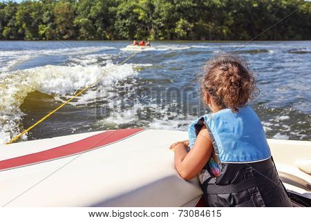 Child in life jacket watching kids riding on a tube pulled by a