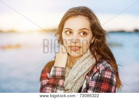 Candid portrait of young brunette woman at sunset looking away with copy space