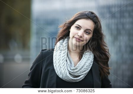 Candid portrait of young brunette woman looking away outside with copy space poster