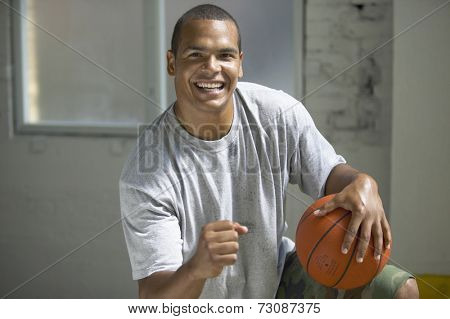 Young man holding basketball and celebrating