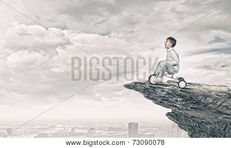 Little joyful cute boy riding tricycle on cliff edge poster