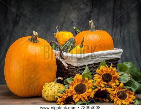 Wicker basket full of summer squashes and pumpkins and bunch of sunflowers over dark gray background poster