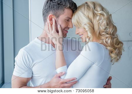 Loving couple enjoy a tender moment touching foreheads and nuzzling as they smile into each others eyes