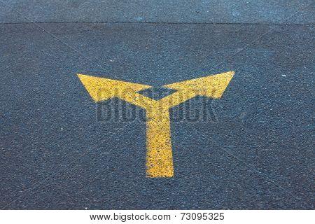Arrow sign on the asphalt road