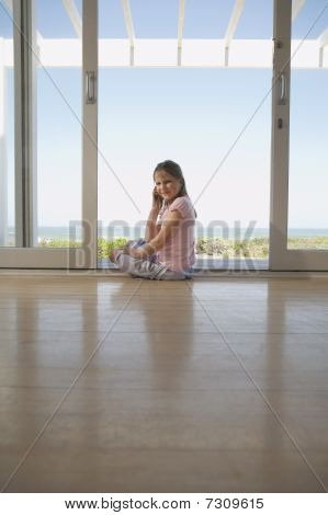 Girl using mobile phone sitting on floor in doorway