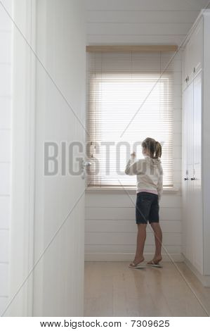 Young girl peering through blinds standing at window full length