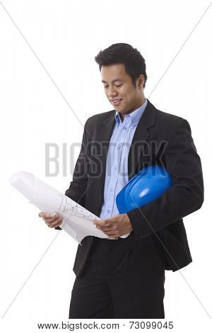 Young Asian architect looking at floor plan, holding hardhat.
