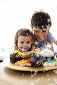 Composite image of Brother and sister looking at confectionery with snow falling poster