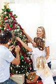 Composite image of Joyful family decorating Christmas tree with snow falling poster