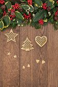 Christmas background border with gold decorations, holly, mistletoe, ivy and fir over old oak. poster