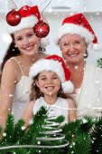 Daughter mother and grandmother baking Christmas sweets against snow falling poster