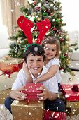Composite image of Happy brother and sister celebrating Christmas with snow falling poster