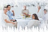 Family smiling at the dinner table against fir tree forest and snowflakes poster