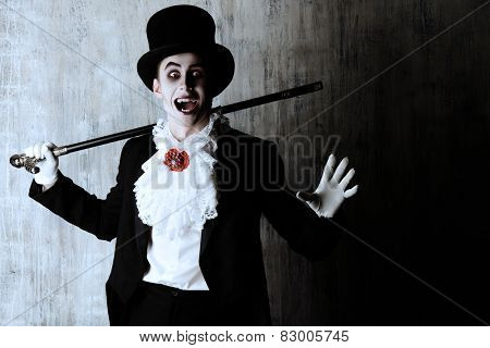 Handsome male vampire in a tail-coat and top-hat. Halloween. Dracula costume.