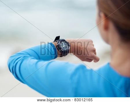 Sporty young woman looking at her watches