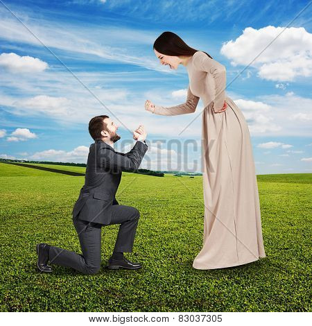 full length portrait of emotional couple at outdoor. woman screaming and showing fist, man standing on knee and apologizing
