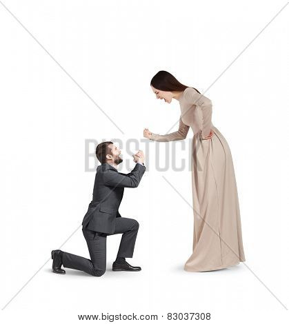 full length portrait of emotional couple isolated on white background. woman screaming and showing fist, man standing on knee and apologizing
