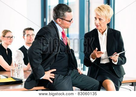 Business - meeting in office, two senior managers are discussing a document on tablet computer poster