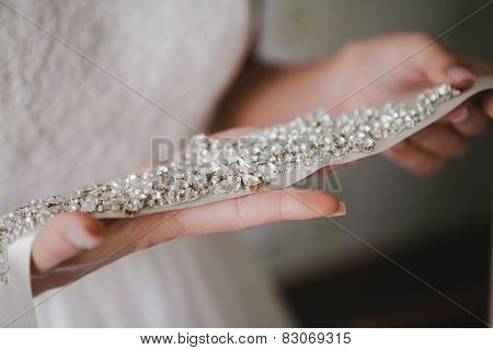 Bride holding a belt with rhinestones. wedding accessories