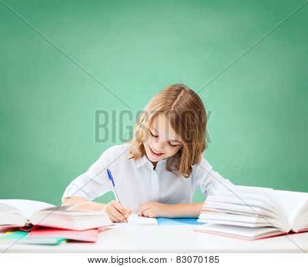 education, people, children and school concept - happy student girl sitting at table with books and writing in notebook over green chalk board background