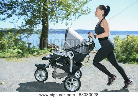A Young mother jogging with a baby buggy poster