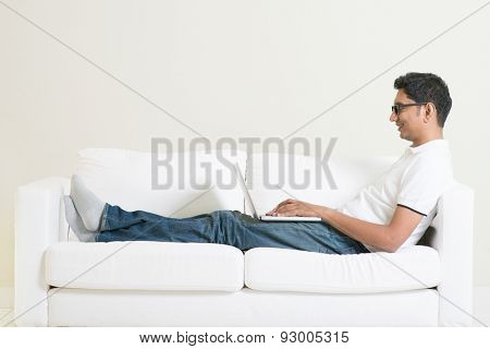 Working from home concept. Indian guy using laptop computer. Asian man relaxed and sitting on sofa indoor. Handsome male model.