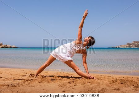 Girl Doing Yoga On A Sandy Beach