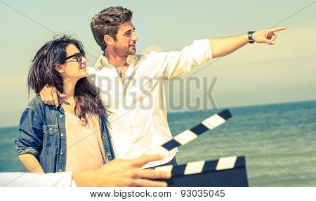 Young Couple In Love Acting For Romantic Film At Beach - Cinema Industry Concept With Ciak Slate Rea